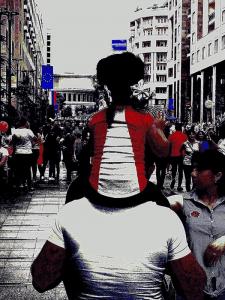 In einer Fußgängerzone. Mädchen sitzt auf den Schultern ihres Vaters. Foto: Christian Callo.