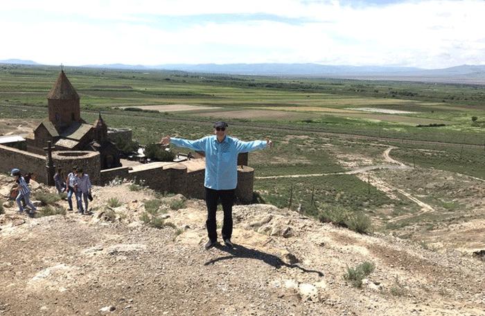 Christian Callo steht mit ausgebreiteten Armen vor den Mauern von Chor Virap. Foto: Christian Callo.