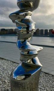 Skulptur mit Stadt im Hintergrund.