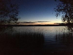 Am Ufer eines Sees bei Abenddämmerung.
