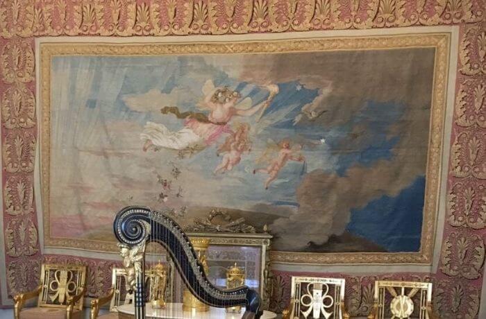 Harfe vor Wandteppich mit Engeln.