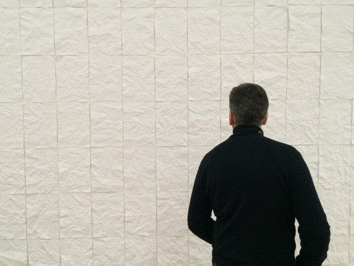 Ein Mann im schwarzen Rollkragenpullover steht vor einer weißen Wand.