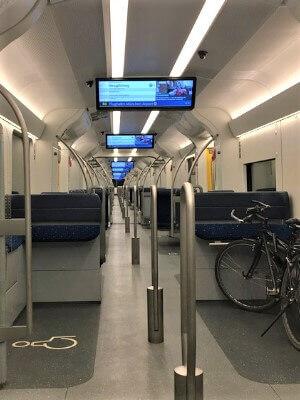 Ein leerer Zug von innen mit einem Fahrrad, es ist draußen dunkel und keine Menschen sind zu sehen.