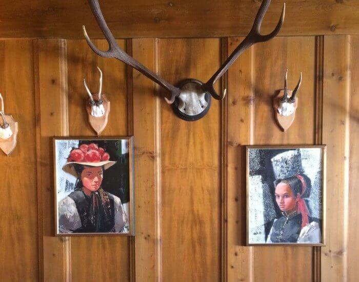 Eine Holzwand mit Bildern von Frauen in der Tracht des Schwarzwalds, darüber Tiergeweihe.