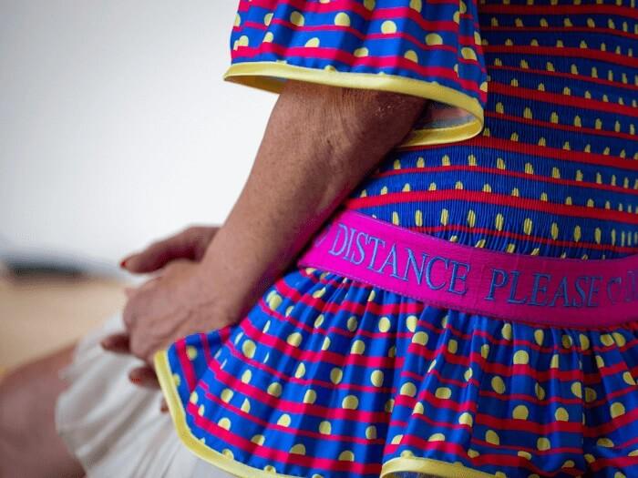 """Eine Frau trägt ein buntes Shirt mit einem pinken Seidengürtel. Auf dem Gürtel steht """"Distance Please""""."""