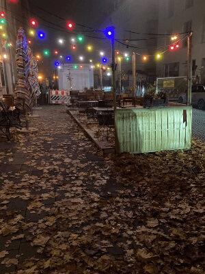 Ein leerer Schanigarten bei Nacht. Eine bunte Lichterkette leuchtet, die Szene sieht trostlos aus.