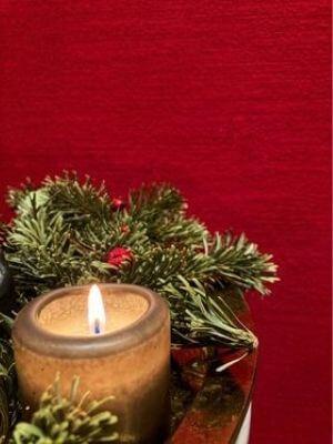 Eine brennende Kerze mit Tannenzweigen vor roter Wand.