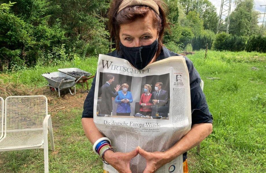Die Autorin Dodo Lazarowicz steht mit Maske und Wirtschaftsteil einer Zeitung in einem Garten.