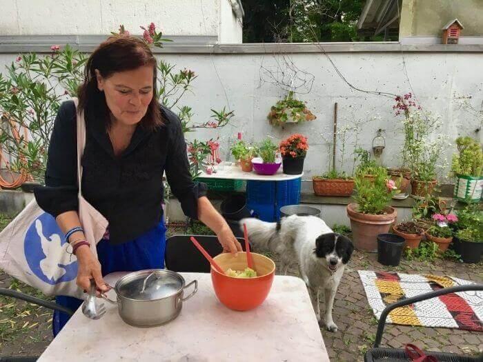 Eine Frau stellt Töpfe und Schüsseln auf einen Tisch in einem Innenhof, neben ihr ein Hund