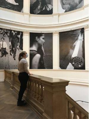 Eine Frau mit Mundschutz steht auf einer Empore in einem Museum, hinter ihr große Fotografien an der Wand.