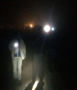 Zwei Menschen mit Taschenlampe machen eine Nachtwanderung.