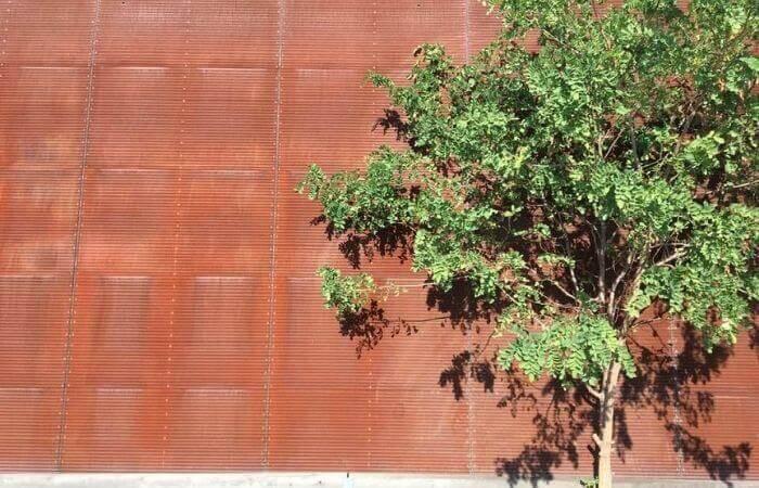 Ein Baum vor einer Wand aus Metallplatten.