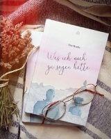 """Ein Buch mit dem Titel """"Was ich noch zu sagen hätte"""" liegt auf einer Decke, darauf eine Brille."""